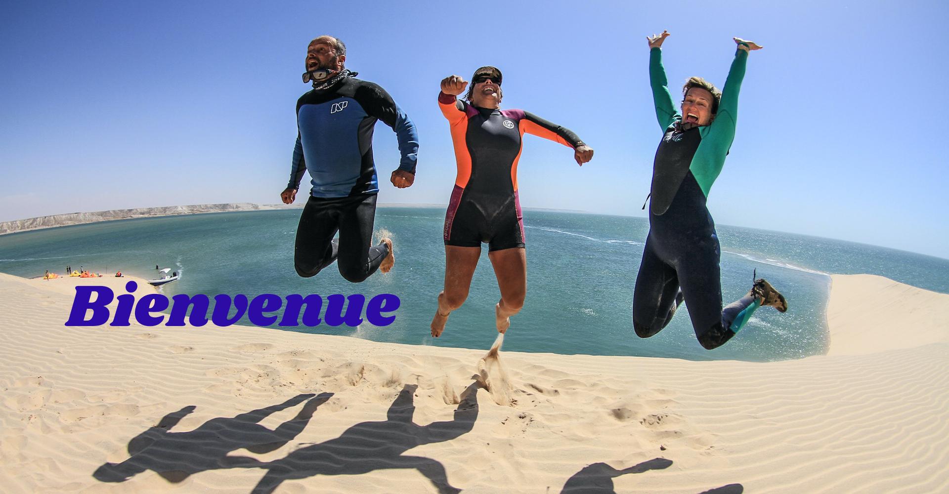 3 amis sautent de joie sur la dune blanche au Maroc